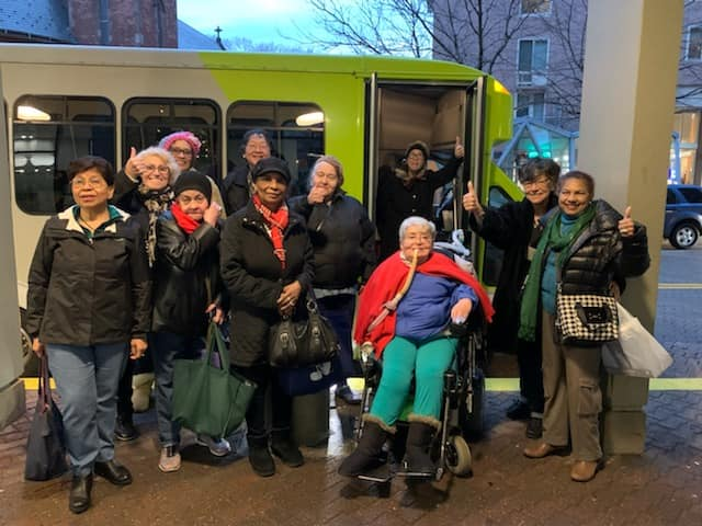 Roosevelt Island Disabled Association (RIDA) gather infront of the used bus they recently purchased from Major Vehicle Exchange